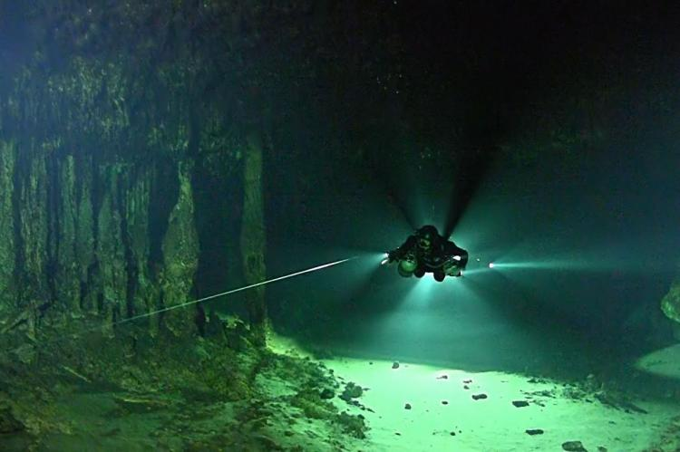 Cave explorer Bil Phillips, also a member of the Texas A&M-led team, uses a flashlight and line to navigate the underwater cave.