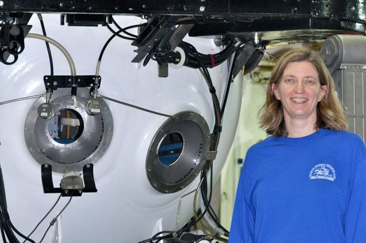 Associate Professor of Earth, Ocean and Atmospheric Science Amy Baco-Taylor, standing next to a submersible in which she has conducted research.
